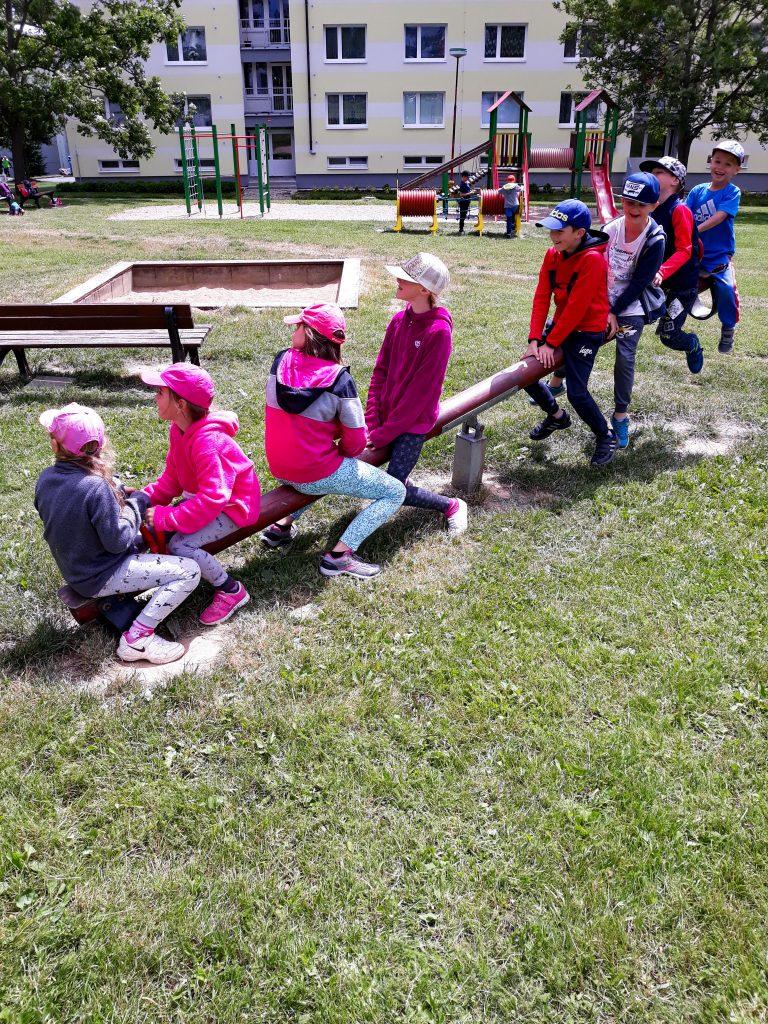 Děti si společně hrají a to díky tomu, že sedí na společné houpačce