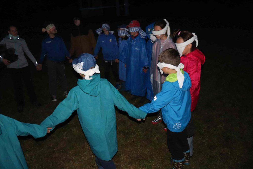 """Noční hra - děti mají zavázané oči a drží se za ruce (tvoří tak """"hada"""")"""