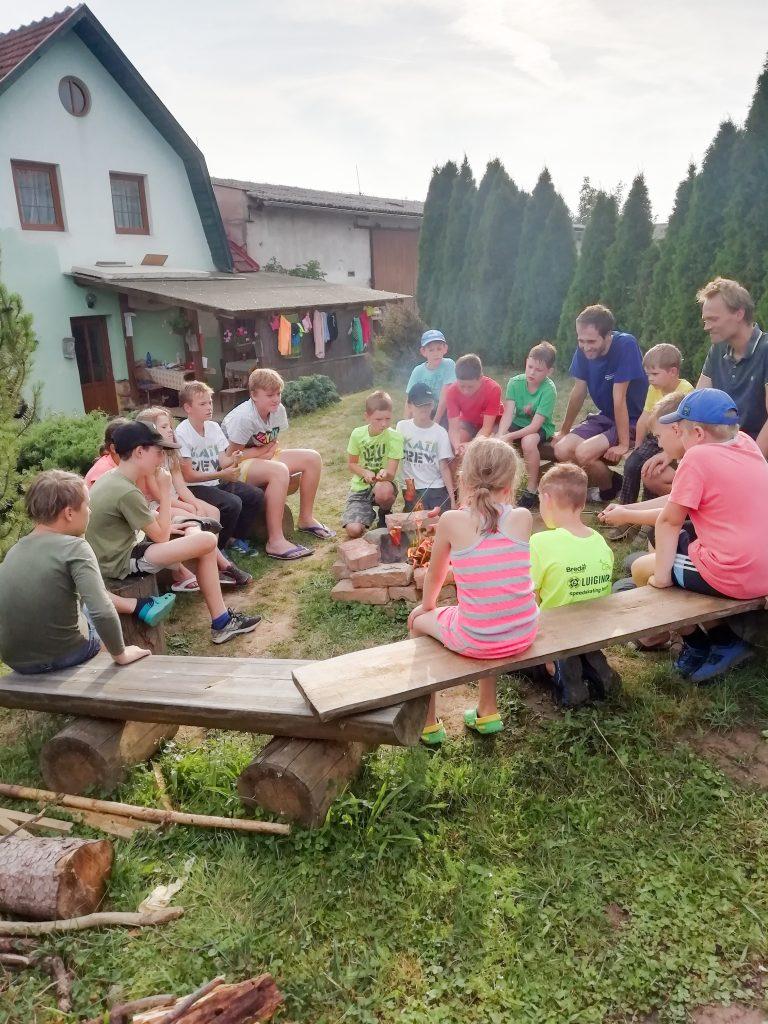 Sezení dětí u ohně a povídání si mezi sebou a s lektory