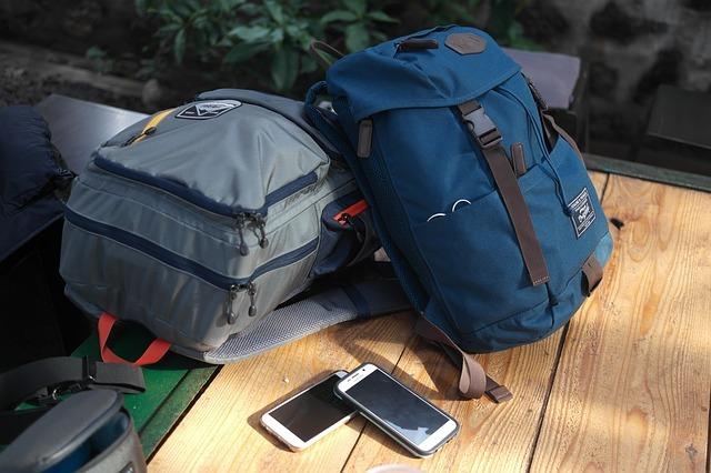 Dva batohy na stole, mobilní telefony vedle nich, protože mobily do táborového batohu nepatří