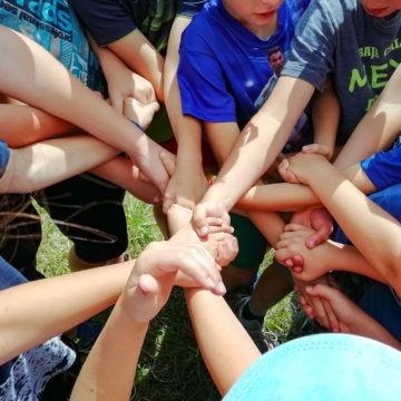 Skupina dětí držejících se za ruce, znázorňuje spolupráci dětí