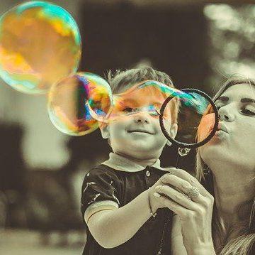 Matka s dítětem a společně foukají bubliny z bublifuku